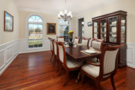 Georgous cherry diningroom table with ivory striped seating with 2 tall arched windows