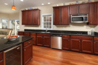 Kitchen area with stainless steel appliances and dark cherry cabinets with black quartz counters
