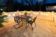 Black metal patio table and setting area with tiled floors, surrounded by a short white fence draped with Christmas lights