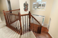 Looking down the entry staircase from the second floor, with oak railing and steps down to the entry area below