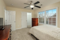 En'suite setting area with light carpeting and dark hard wood furniture, including flat screen TV and walk-in closet