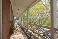 View of porch with rocking chairs.
